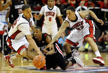 LAS VEGAS - MARCH 13:  D.J. Gay #23 of the San Diego State Aztecs loses the ball under pressure from Chace Stanback #22 and Tre'Von Willis #33 of the UNLV Rebels during the championship game of the Conoco Mountain West Conference Basketball tournament at