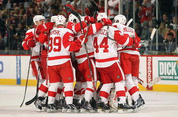 DENVER - DECEMBER 27:  The Detroit Red Wings mob their goalie Chris Osgood #30 of the Detroit Red Wings after he earned his 400th win with a victory over the Colorado Avalanche at the Pepsi Center on December 27, 2010 in Denver, Colorado. Osgood collected