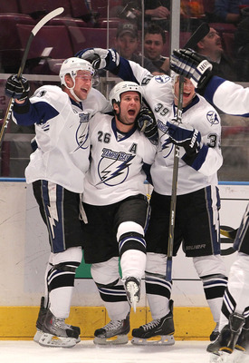 NEW YORK, NY - DECEMBER 23: Steven Stamkos #91, Martin St. Louis #26, and Mike Lundin #39 of the Tampa Bay Lightning celebrate a goal by St. Louis during an NHL hockey game against the New York Rangers at Madison Square Garden on December 23, 2010 in New