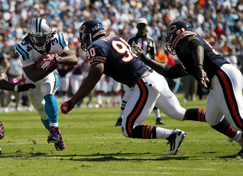 CHARLOTTE, NC - OCTOBER 10: Running back DeAngelo Williams #34 of the Carolina Panthers runs with the ball as defensive end Julius Peppers #90 of the Chicago Bears defends at Bank of America Stadium on October 10, 2010 in Charlotte, North Carolina. (Photo