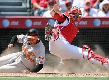 ANAHEIM, CA - AUGUST 29:  Josh Bell #25 f the Baltimore Orioles is tagged out at home plate by Jeff Mathis #5 of the Los Angeles Angels of Anaheim during the sixth inning at Angel Stadium on August 29, 2010 in Anaheim, California.  (Photo by Harry How/Get