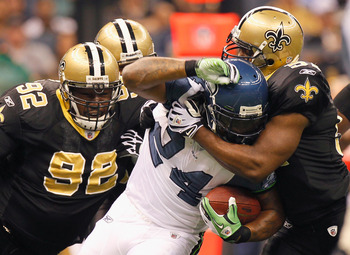 NEW ORLEANS - NOVEMBER 21:  Jonathan Vilma #51 and Remi Ayodele #92 of the New Orleans Saints tackle Marshawn Lynch #24 of the Seattle Seahawks at Louisiana Superdome on November 21, 2010 in New Orleans, Louisiana.  (Photo by Kevin C. Cox/Getty Images)