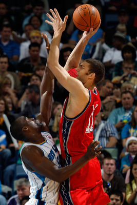 NEW ORLEANS, LA - DECEMBER 22:  Brook Lopez #11 of the New Jersey Nets shoots the ball over Emeka Okafor #50 of the New Orleans Hornets at the New Orleans Arena on December 22, 2010 in New Orleans, Louisiana.    The Hornets defeated the Nets 105-91.   NOT