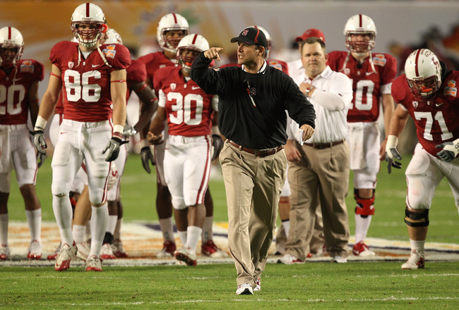 MIAMI, FL - JANUARY 03:  Head coach Jim Harbaugh of the Stanford Cardinal instructs his players during warm ups against the Virginai Tech Hokies during the 2011 Discover Orange Bowl at Sun Life Stadium on January 3, 2011 in Miami, Florida.  (Photo by Stre