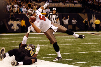 NEW ORLEANS, LA - JANUARY 02:  Quarterback Josh Freeman #5 of the Tampa Bay Buccaneers is pulled down by Alex Brown #96 of the New Orleans Saints at the Louisiana Superdome on January 2, 2011 in New Orleans, Louisiana.  The Buccaneers defeated the Saints