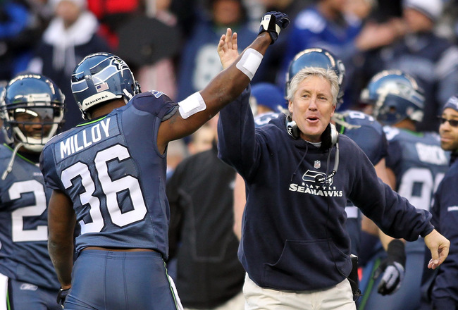 SEATTLE, WA - JANUARY 08:  Head coach Pete Carroll and Lawyer Milloy #36 of the Seattle Seahawks celebrate a fourth down stop by the Seahawks in the third quarter against the New Orleans Saints during the 2011 NFC wild-card playoff game at Qwest Field on
