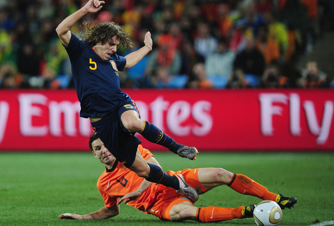 JOHANNESBURG, SOUTH AFRICA - JULY 11: Mark Van Bommel of the Netherlands tackles Carles Puyol of Spain during the 2010 FIFA World Cup South Africa Final match between Netherlands and Spain at Soccer City Stadium on July 11, 2010 in Johannesburg, South Afr