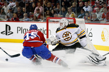 MONTREAL, CANADA - JANUARY 8:  Tim Thomas #30 of the Boston Bruins stretches out to stop the puck in front of Jeff Halpern #15 of the Montreal Canadiens during the NHL game at the Bell Centre on January 8, 2011 in Montreal, Quebec, Canada.  (Photo by Rich
