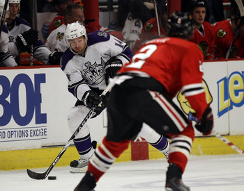 CHICAGO, IL - DECEMBER 19: Justin Williams #14 of the Los Angeles Kings passes the puck near Duncan Keith #2 of the Chicago Blackhawks at the United Center on December 19, 2010 in Chicago, Illinois. The Blackhawks defeated the Kings 3-2. (Photo by Jonatha