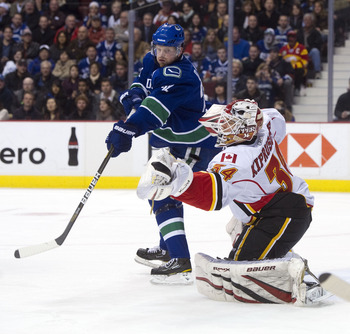 VANCOUVER, CANADA - JANUARY 5: Daniel Sedin #22 of the Vancouver Canucks deflects the puck past goalie Miikka Kiprusoff #34 of the Calgary Flames during the second period in NHL action on January 05, 2011 at Rogers Arena in Vancouver, BC, Canada.  (Photo