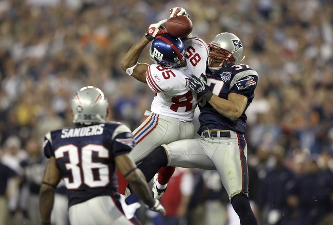 GLENDALE, AZ - FEBRUARY 03:  David Tyree #85 of the New York Giants catches a 32-yard pass from Eli Manning #10 against Rodney Harrison #37 and James Sanders #36 of the New England Patriots attempts to knock it out in the fourth quarter of Super Bowl XLII