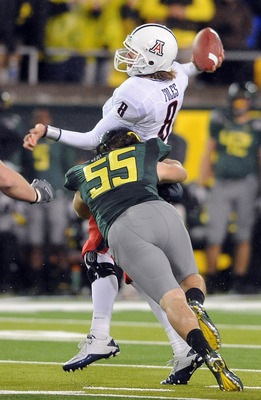 EUGENE, OR - NOVEMBER 26: Quarterback Nick Foles #8 of the Arizona Wildcats is hit by linebacker Casey Matthews #55 of the Oregon Ducks as he throws a pass in the third quarter of the game at Autzen Stadium on November 26, 2010 in Eugene, Oregon.The Ducks