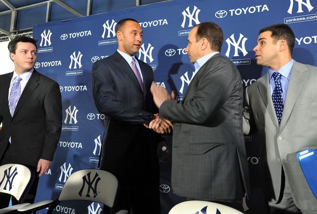 TAMPA, FL - DECEMBER 07:   Shortstop Derek Jeter of the New York Yankees (2L) shakes hands with General Manager Brian Cashman (2R) during a press conference to announce his new contract with the club on December 7, 2010 in Tampa, Florida.  (Photo by Tim B