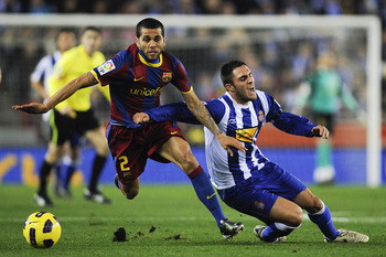 BARCELONA, SPAIN - DECEMBER 18: Dani Alves of Barcelona (L) and Victor Ruiz of Espanyol duel for a ball during the La Liga match between Espanyol and Barcelona at Cornella - El Prat stadium on December 18, 2010 in Barcelona, Spain. Barcelona won the match