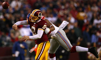 LANDOVER, MD - JANUARY 02:  Quarterback Rex Grossman #8 of the Washington Redskins  is hit by defensive end Osi Umenyiora #72 of the New York Giants during a game at FedEx Field on January 2, 2011 in Landover, Maryland. The Giants won the game 17-14.  (Ph