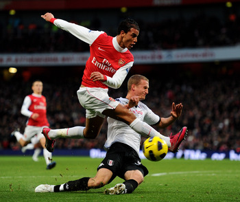 LONDON, ENGLAND - DECEMBER 04:  Marouane Chamakh (L) of Arsenal is tackled by Brede Hangeland of Fulham during the Barclays Premier League match between Arsenal and Fulham at the Emirates Stadium on December 4, 2010 in London, England.  (Photo by Mike Hew