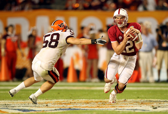 MIAMI, FL - JANUARY 03: Andrew Luck #12 of the Stanford Cardinal ellude Jack Tyler #58 of the Virginia Tech Hokies during the 2011 Discover Orange Bowl at Sun Life Stadium on January 3, 2011 in Miami, Florida. STanford won 40-12. (Photo by Mike Ehrmann/Ge
