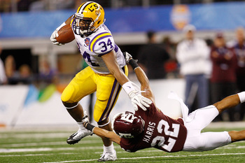 ARLINGTON, TX - JANUARY 07:  Stevan Ridley #34 of the Louisiana State University Tigers avoids a tackle by Dustin Harris #22 of the Texas A&M Aggies during the AT&T Cotton Bowl at Cowboys Stadium on January 7, 2011 in Arlington, Texas.  (Photo by Chris Gr