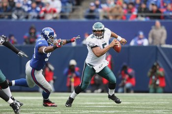 EAST RUTHERFORD, NJ - DECEMBER 7:  Quarterback Donovan McNabb #5 of the Philadelphia Eagles scrambles as he looks to pass the ball against Justin Tuck #91 of the New York Giants at Giants Stadium on December 7, 2008 in East Rutherford, New Jersey. (Photo