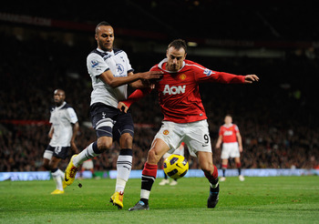 MANCHESTER, ENGLAND - OCTOBER 30: Dimitar Berbatov of Manchester United is challenged by Younes Kaboul of Tottenham during the Barclays Premier League match between Manchester United and Tottenham Hotspur at Old Trafford on October 30, 2010 in Manchester,