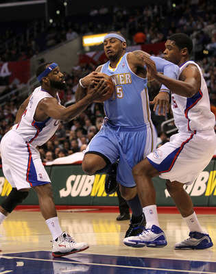 LOS ANGELES, CA - JANUARY 05:  Carmelo Anthony #15 of the Denver Nuggets fights to drive through Baron Davis #5 and Ryan Gomes #15 of the Los Angeles Clippers at Staples Center on January 5, 2011  in Los Angeles, California.  NOTE TO USER: User expressly