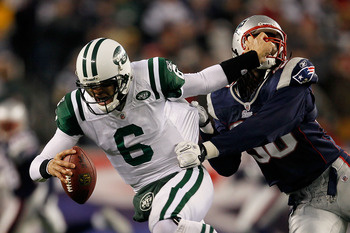FOXBORO, MA - DECEMBER 06:  Mark Sanchez #6 of the New York Jets attempts to escape the pass rush of Jermaine Cunningham #96 of the New England Patriots at Gillette Stadium on December 6, 2010 in Foxboro, Massachusetts.  (Photo by Jim Rogash/Getty Images)