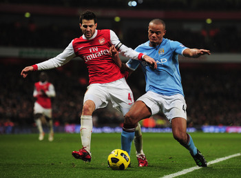 LONDON, ENGLAND - JANUARY 05:  Cesc Fabregas of Arsenal battles with Vincent Kompany of Manchester City during the Barclays Premier League match between Arsenal and Manchester City at the Emirates Stadium on January 5, 2011 in London, England.  (Photo by