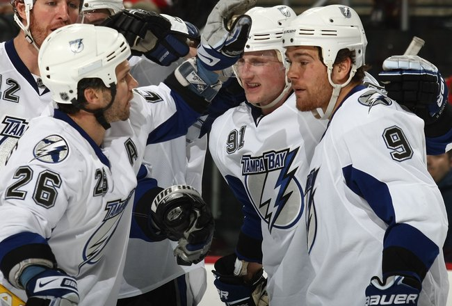 NEWARK, NJ - DECEMBER 04: (L-R) Martin St. Louis #26, Steven Stamkos #91 and Steve Downie #9 of the Tampa Bay Lightning celebrate a goal against the New Jersey Devils at the Prudential Center on December 4, 2009 in Newark, New Jersey. (Photo by Bruce Benn