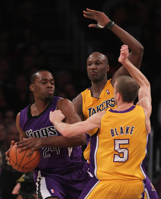 LOS ANGELES, CA - DECEMBER 03:  (L-R) Carl Landry #24 of the Sacramento Kings is defended by Lamar Odom #7 and Steve Blake #5 of the Los Angeles Lakers during the first half at Staples Center on December 3, 2010 in Los Angeles, California. The Lakers defe