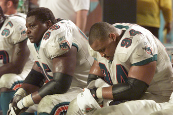 13 Jan 2001:  Tim Bowens #95 and teammate Jermaine Haley #94 of the Miami Dolphins look dejected as they watch their team loose to the Baltimore Ravens during the AFC Playoff game at Pro Player Stadium in Miami, Florida. The Ravens won 20-3. DIGITAL IMAGE