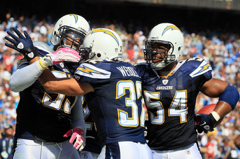 SAN DIEGO - OCTOBER 03:  Eric Weddle #32 and Stephen Cooper #54 of the San Diego Chargers congratulate teammate Shaun Phillips #95 after intercepting a pass for a touchdown against the Arizona Cardinals at Qualcomm Stadium on October 3, 2010 in San Diego,