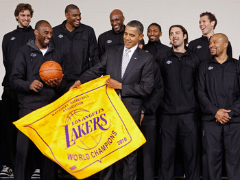 WASHINGTON, DC - DECEMBER 13:  (AFP OUT) U.S. President Barack Obama (C) receives an autographed championship flag and basketball from members of the Los Angeles Lakers (L-R) Paul Gasol, Kobe Bryant, Andrew Bynum, Lamar Odom, Ron Artest, Aleksandar Vujaci