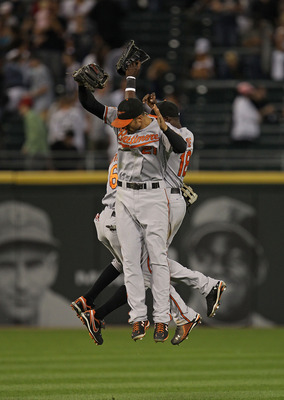 CHICAGO - AUGUST 25: (L-R) Cory Patterson #6, Nick Markakis #21 and Felix Pie #18 of the Baltimore Orioles leap in celebration after a win over the Chicago White Sox at U.S. Cellular Field on August 25, 2010 in Chicago, Illinois. The Orioles defeated the