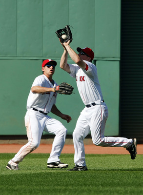 BOSTON - JULY 05:  J.D. Drew #7 of the Boston Red Sox makes the catch for the out as teammate Jacoby Ellsbury #46 looks on in the ninth inning against the Seattle Mariners on July 5, 2009 at Fenway Park in Boston, Massachusetts. The Red Sox defeated the M