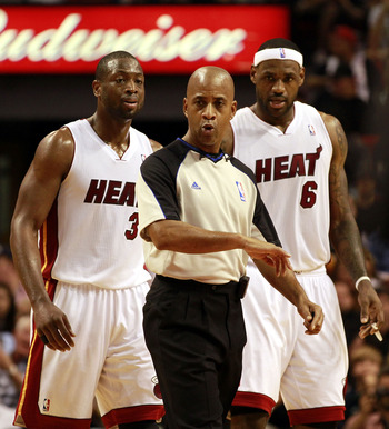 MIAMI - JANUARY 01: LeBron James #6 and Dwyane Wade #3 of the Miami Heat stand behind a referee during the game against the Golden State Warriors at American Airlines Arena on January 1, 2011 in Miami, Florida. The Heat won 114-107. NOTE TO USER: User exp