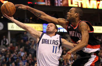 DALLAS, TX - JANUARY 04:  Guard Jose Juan Barea #11 of the Dallas Mavericks takes a shot against Marcus Camby #23 of the Portland Trail Blazers at American Airlines Center on January 4, 2011 in Dallas, Texas.  NOTE TO USER: User expressly acknowledges and