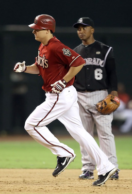 PHOENIX - SEPTEMBER 22:  Kelly Johnson #2 of the Arizona Diamondbacks rounds the bases past infielder Melvin Mora #6 of the Colorado Rockies after hitting a 2 run home run during the eighth inning of the Major League Baseball game at Chase Field on Septem
