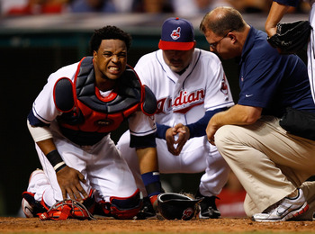 CLEVELAND - JULY 29:  Carlos Santana #41 of the Cleveland Indians grimaces in pain in front of Manager Manny Acta #11 after a ball hit him in the knee during the game against the New York Yankees on July 29, 2010 at Progressive Field in Cleveland, Ohio.