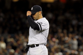 NEW YORK - OCTOBER 18:  Andy Pettitte #46 of the New York Yankees adjusts his cap as he reacts against the Texas Rangers in Game Three of the ALCS during the 2010 MLB Playoffs at Yankee Stadium on October 18, 2010 in New York, New York.  (Photo by Nick La
