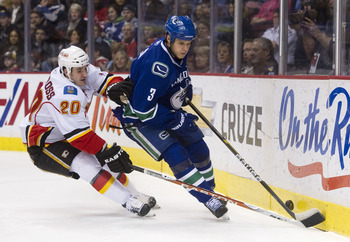 VANCOUVER, CANADA - JANUARY 5: Kevin Bieksa #3 of the Vancouver Canucks tries to control the bouncing puck while being checked by Curtis Glencross #20 of the Calgary Flames during the first period in NHL action on January 05, 2011 at Rogers Arena in Vanco