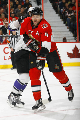 OTTAWA, ON - NOVEMBER 22:  Chris Phillips #4 of the Ottawa Senators throws the shoulder into Jarret Stoll #28 of the Los Angeles Kings during a game at Scotiabank Place on November 22, 2010 in Ottawa, Ontario, Canada.  (Photo by Phillip MacCallum/Getty Im