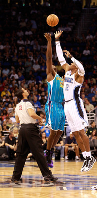 ORLANDO, FL - OCTOBER 10:  Dwight Howard #12 of the Orlando Magic jumps against  Emeka Okafor #50 of the New Orleans Hornets during the game at Amway Arena on October 10, 2010 in Orlando, Florida. NOTE TO USER: User expressly acknowledges and agrees that,