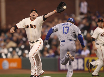 SAN FRANCISCO - SEPTEMBER 16:  Aubrey Huff #17 of the San Francisco Giants can't reach an error thrown by Juan Uribe in the first inning as Ryan Theriot #13 of the Los Angeles Dodgers is safe at first during a Major League Baseball game at AT&T Park on Se