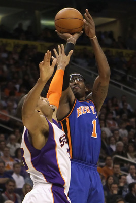 PHOENIX - JANUARY 07:  Amar'e Stoudemire #1 of the New York Knicks puts up a shot over Grant Hill #33 of the Phoenix Suns during the NBA game at US Airways Center on January 7, 2011 in Phoenix, Arizona.  NOTE TO USER: User expressly acknowledges and agree