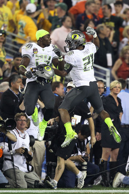 GLENDALE, AZ - JANUARY 10:  (R-L) LaMichael James #21 and Kenjon Barner #24 of the Oregon Ducks celebrate James' eight-yard touchdown reception in the second quarter against the Auburn Tigers during the Tostitos BCS National Championship Game at Universit
