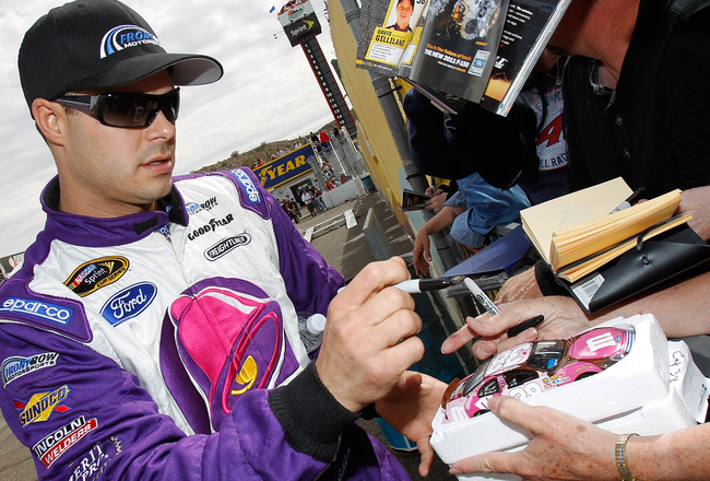 AVONDALE, AZ - FEBRUARY 26:  David Gilliland, driver of the #34 Taco Bell Ford, signs autographs for fans during qualifying for the NASCAR Sprint Cup Series Subway Fresh Fit 500 at Phoenix International Raceway on February 26, 2011 in Avondale, Arizona.
