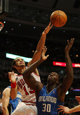 CHICAGO, IL - DECEMBER 01: Joakim Noah #13 of the Chicago Bulls knocks the ball away from Brandon Bass #30 of the Orlando Magic at the United Center on December 1, 2010 in Chicago, Illinois. NOTE TO USER: User expressly acknowledges and agrees that, by do