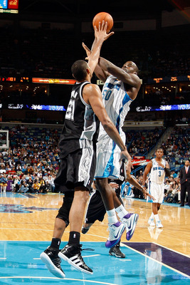 NEW ORLEANS - NOVEMBER 28:  Emeka Okafor #50 of the New Orleans Hornets shoots the ball over Tim Duncan #21 of the San Antonio Spurs at the New Orleans Arena on November 28, 2010 in New Orleans, Louisiana.  NOTE TO USER: User expressly acknowledges and ag