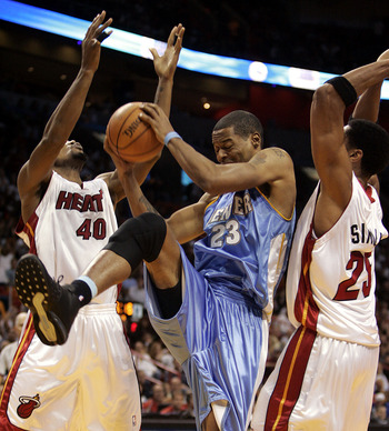 MIAMI - DECEMBER 9:  Center Marcus Camby #23 of the Denver Nuggets grabs the ball between forward Udonis Haslem #40 and forward Wayne Simien #25 of the Miami Heat on December 9, 2005 at the American Airlines Arena in Miami, Florida. NOTE TO USER: User exp