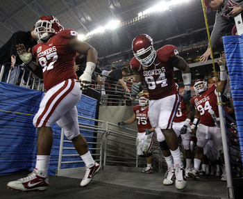 GLENDALE, AZ - JANUARY 01:  Jamarkus McFarland #97 and Pryce Macon #94 of the Oklahoma Sooners run out of the tunnel after the half to take on the Connecticut Huskies  during the Tostitos Fiesta Bowl at the Universtity of Phoenix Stadium on January 1, 201